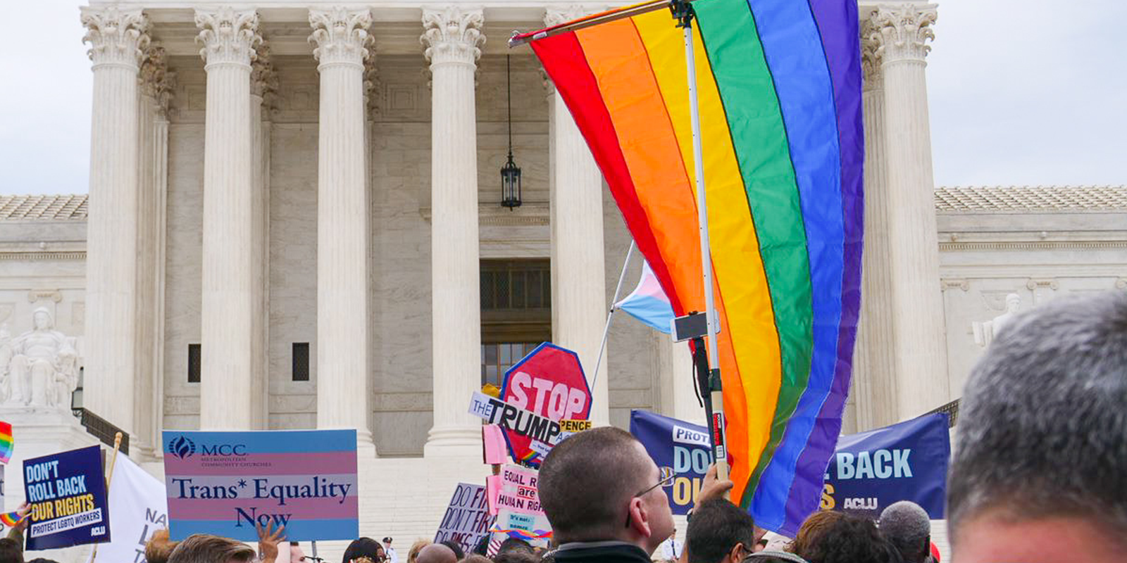 Gay pride flag in front of supreme court entrance with pro-LGBTQ equality signs